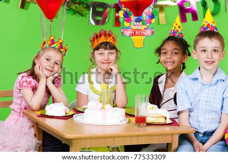 Sweet friends sitting at the table and eating  birthday cake - stock photo