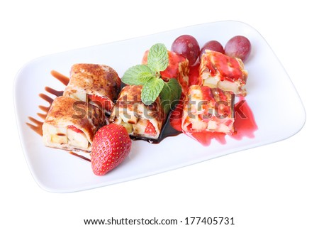 Sweet fruit roll with Banana, strawberry and grapes, wrapped in pancake  under chocolate sauce and  red berry jam on white rectangular dish isolated on a white background. Side view. - stock photo