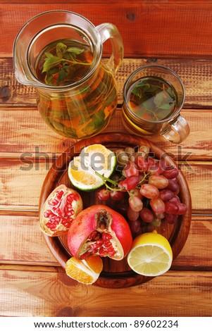 sweet fruits with tea pot on wood - stock photo