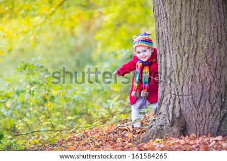 Sweet funny baby girl in a red coat and colorful hat and knitted scarf hiding behind a big old tree in a beautiful autumn park with yellow leaves - stock photo