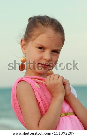 Sweet gentle young girl with a sweet smile and beautiful earrings on a background sea shore - stock photo