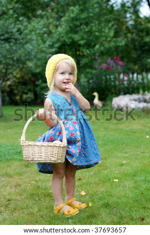 Sweet girl and basket with apples - stock photo