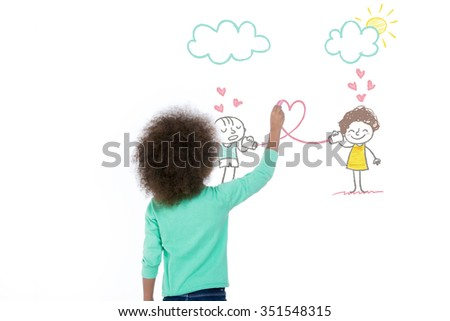 sweet girl drawing two little children on a wall - stock photo