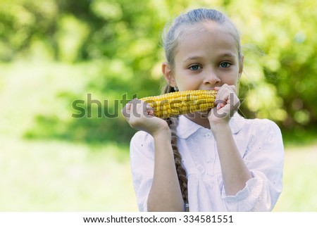 Sweet girl eating corn outdoors - stock photo