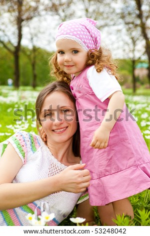 Sweet girl embracing her mother on the meadow - stock photo