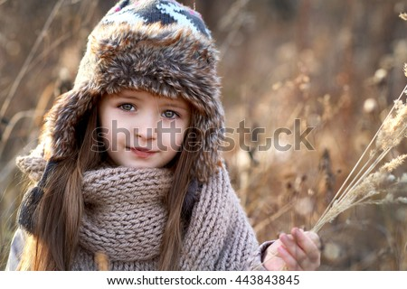 Sweet girl in a cap with the deer in autumn in a field of dry grass - stock photo