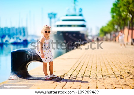 sweet girl in a dock, big cruise ship on background - stock photo