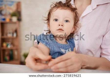 Sweet girl in her mother arms - stock photo