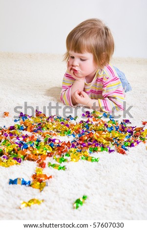 Sweet girl looking at candies and making choice - stock photo