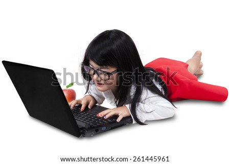 Sweet girl lying on the floor while typing on laptop computer, isolated over white background