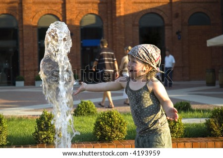 sweet girl playing in a public fountain. summer scenic. childhood