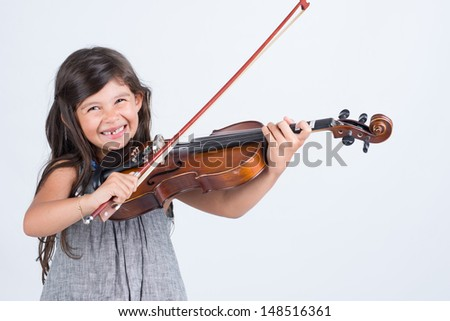 Sweet girl playing musical instrument - stock photo