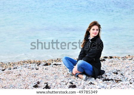 sweet girl relaxing on the beach in spring time