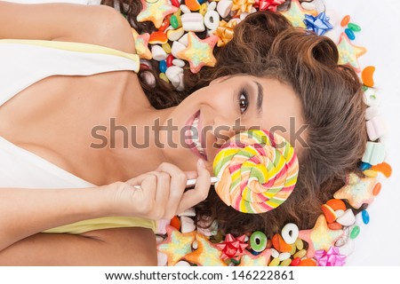 Sweet girl. Top view of beautiful young women holding a lollipop in front of her eye while lying on the floor covered with candies - stock photo