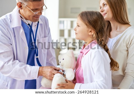 Sweet girl with teddybear looking at doctor with her mother near by