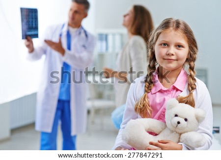 Sweet girl with white teddy looking at camera with her doctor talking to woman on background - stock photo