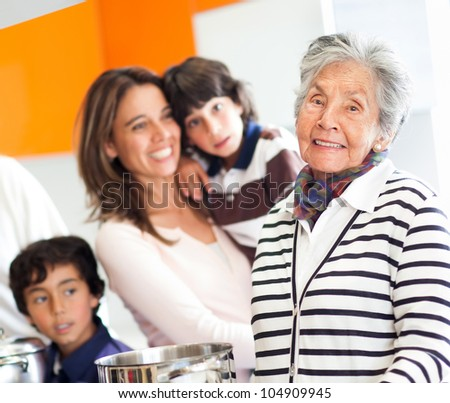 Sweet grandmother cooking for the family and smiling - stock photo