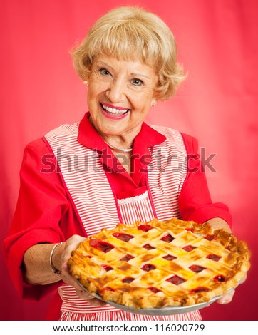 Sweet grandmother in vintage apron holding a delicious homemade cherry pie. - stock photo
