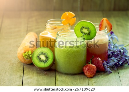 Sweet green color of mix fruit juice blended on wooden background - stock photo