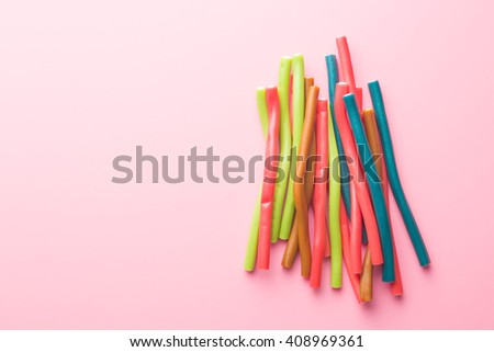 Sweet gummy sticks with different flavor. Top view of tasty candy on pink background. - stock photo