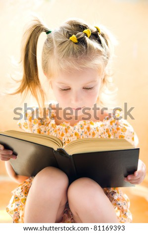 sweet happy little girl reading a book - stock photo