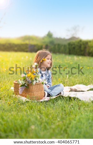 Sweet, happy, smiling six year old girl sitting on a grass in a park and laughing,colored photo