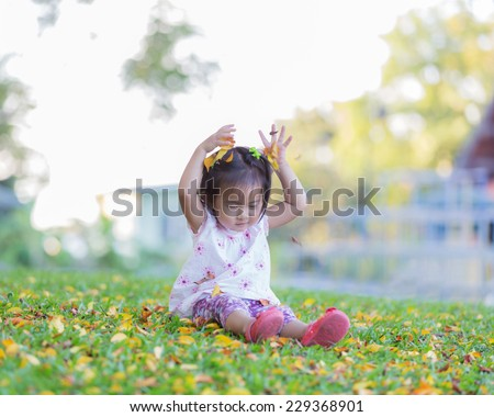 Sweet, happy, smiling two year old girl lying on a grass in a park playing throw dry leaf - stock photo