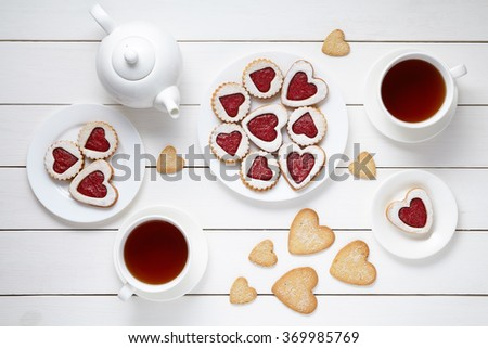 Sweet heart cookies for Valentines day with teapot and two cups of tea composition on white wooden background - stock photo