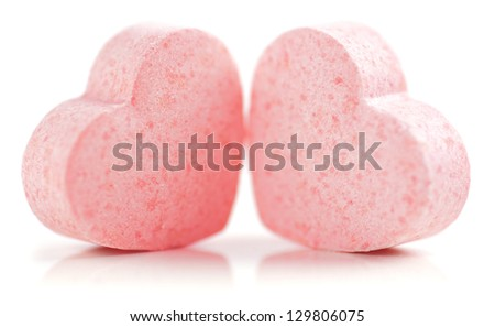 Sweet hearts shaped pink Sugar Pills on white background. Soft Focus. - stock photo