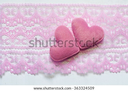 Sweet holiday background with pink hearts and pink lace fabric.