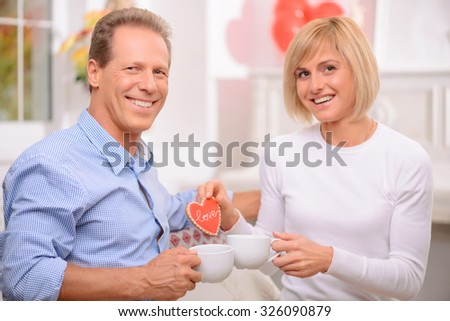 Sweet home. Upbeat delighted adult couple drinking tea and relaxing at home while expressing joy - stock photo