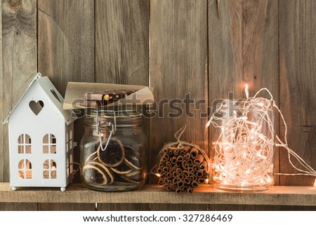 Sweet home. White Christmas decor on vintage natural wooden background. Cinnamon sticks and dried citrus. Cafe shelf. - stock photo