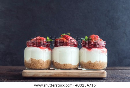 Sweet homemade cheesecake with strawberries in the jar on wooden background,selective focus - stock photo