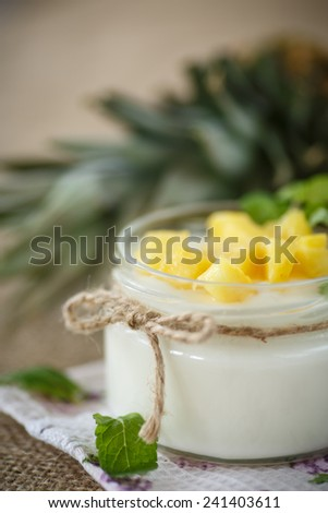 sweet homemade yogurt with pineapple in a glass jar - stock photo