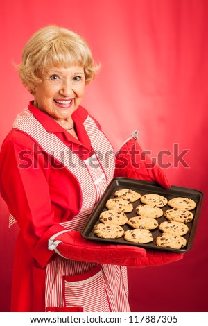 Sweet homemaker grandma holding a tray of fresh baked chocolate chip cookies.  Photographed in front of red background. - stock photo