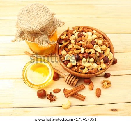 Sweet honey and different nuts on wooden table - stock photo