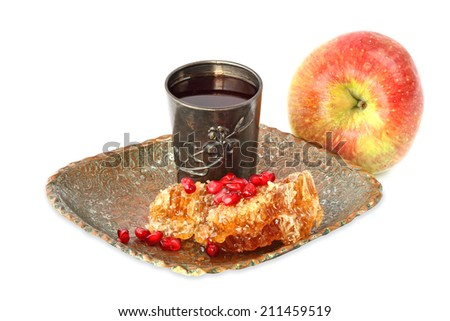 Sweet honey comb with honey, pomegranate grains, silver glass with wine and apple fruit - Jewish traditional food for the holiday of Rosh Hashana (Jewish new year). Isolated on white.  - stock photo