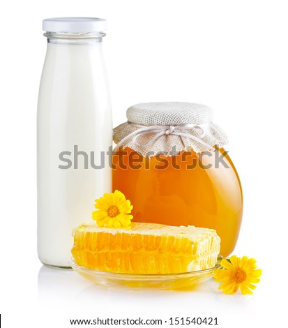 Sweet honey in glass jars with flowers, honeycombs and bottle of milk isolated on white - stock photo