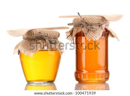 Sweet honey in jars with spoons isolated on white - stock photo