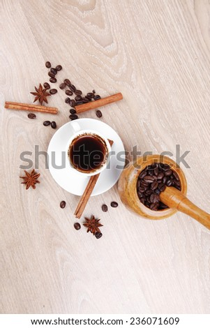 sweet hot drink : black arabic coffee in small white cup with mortar and pestle , beans spilled over wooden table , decorated with cinnamon sticks and anise stars - stock photo