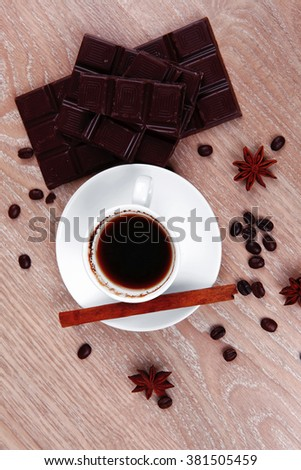 sweet hot drink black Turkish coffee in small white mug with coffee beans spilled over a wooden table with stripes of dark chocolate and cinnamon stick