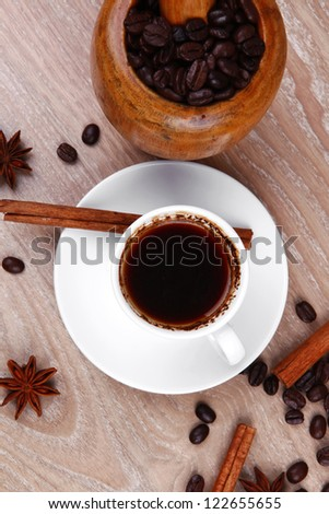 sweet hot drink : black Turkish coffee in small white mug with mortar and pestle , coffee beans over a wooden table , decorated with cinnamon sticks and anise stars