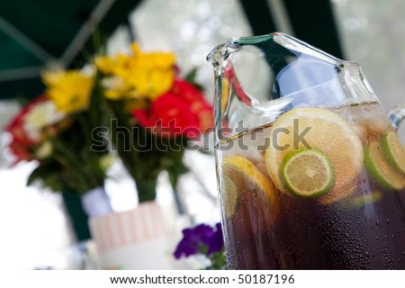 Sweet iced tea in a glass pitcher with lemon and lime fruit slices floating with a flower bouquet in the background