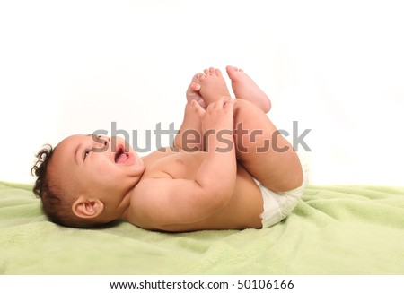 Sweet Infant Happily Shrieking in Laughter While Lying Down Holding His Feet - stock photo