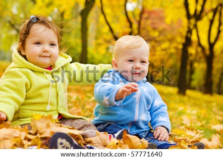 Sweet kids sitting on the autumn leaves - stock photo