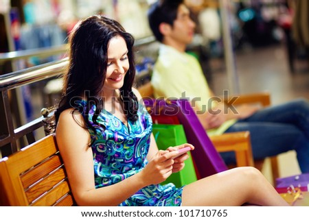 Sweet lady typing a short message on her mobile phone, her male friend can be seen in the background, shopping series - stock photo
