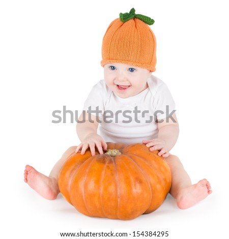 Sweet laughing baby girl playing with a huge pumpkin wearing a knitted pumpkin hat on white background - stock photo
