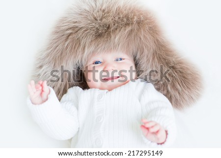 Sweet laughing baby in a big fur hat - stock photo