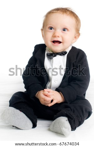 sweet laughing baby in tailcoat sitting on white ground - stock photo