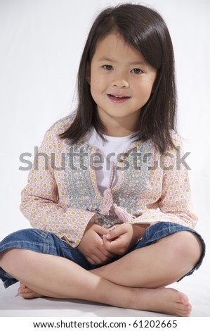 Sweet little Asian Girl sitting on a white background - stock photo